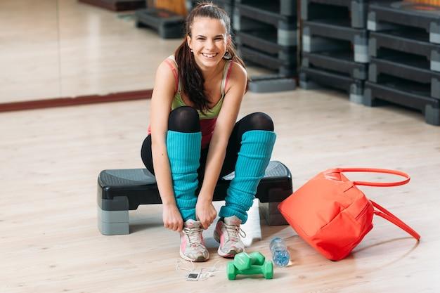 Счастливая женщина надевает кроссовки для тренировки