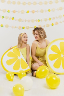 Happy woman and girl posing with lemon decorations and balloons