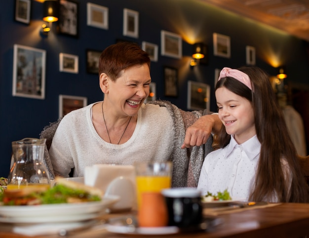 Happy woman and girl at table