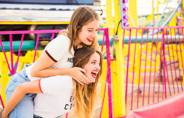 Happy woman giving piggyback to her female friend