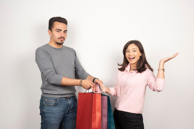 Happy woman giving shopping bags to tired man to carry.