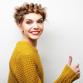 親指をあきらめる幸せな女性。ライフスタイルの写真。