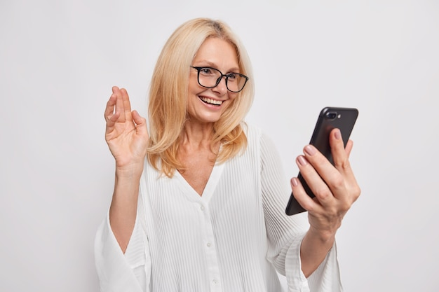 Happy woman glad to make distance call has online comversation with daughter waves palm in hello gesture holds mobile phone uses high speed internet connection wears silk white blouse glasses