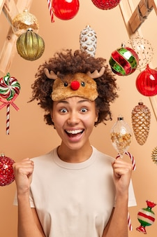 Happy woman glad to win new year lottery raises clenched fists and exclaims with joy has good luck spends leisure time at home awaits for holidays or midnight stroke. yeah finally feast is coming!
