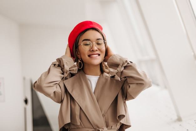 Happy woman in glasses smiling against window