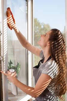 Happy woman in gloves cleaning window with rag and cleanser spray at home