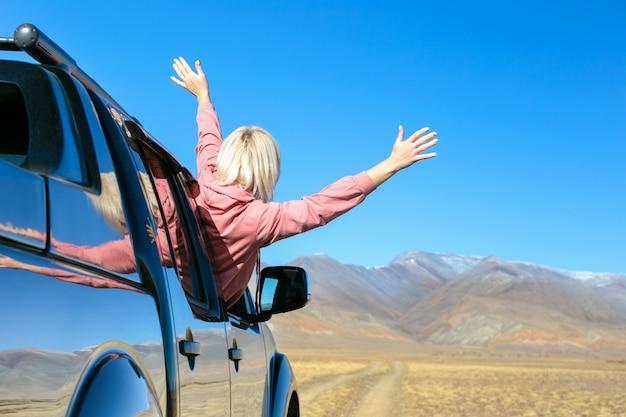 행복 한 여자는 차에 여름 또는 가을 여행 여행에 간다.