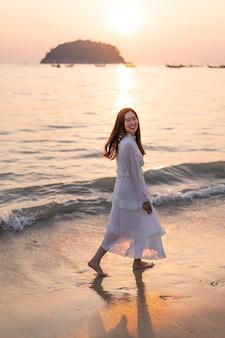 Счастливая женщина собирается путешествовать на тропическом песчаном пляже летом