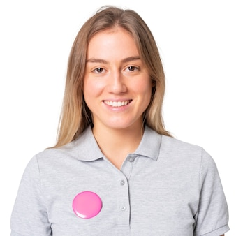 Happy woman in gray polo shirt with pink pin button