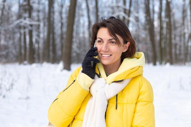 Donna felice di ottimo umore cammina attraverso la foresta invernale innevata e chiacchiera allegramente al telefono, godendosi il tempo all'aperto nel parco