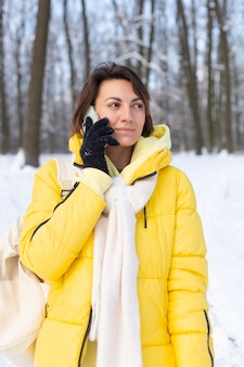 Happy woman in a great mood walks through the snowy winter forest and chatting cheerfully on the phone, enjoying time outdoors in the park