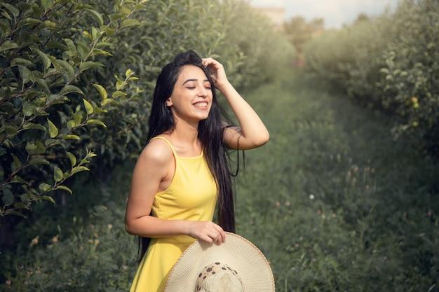 Счастливая женщина рука шляпа в саду