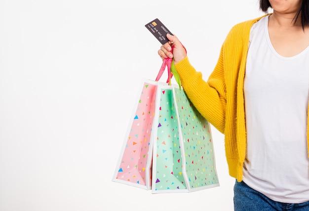 Счастливая женщина рука она носит желтую рубашку, держа разноцветные хозяйственные сумки и кредитную карту