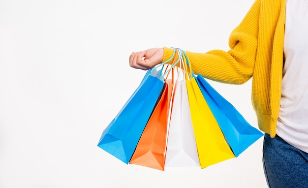 Happy woman hand she wears yellow shirt holding shopping bags multicolor