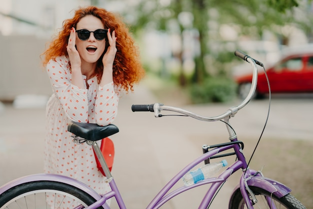 Happy woman has curly foxy hair, leans at saddle of her bicycle,