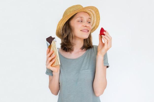 Donna felice in cappello che tiene fragola e cioccolato maturi