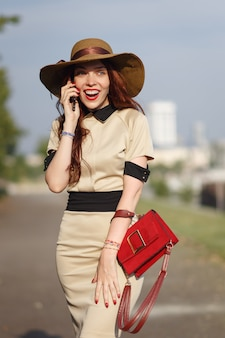 A happy woman in a hat is walking in the park in the summer with a bag and talking on the phone