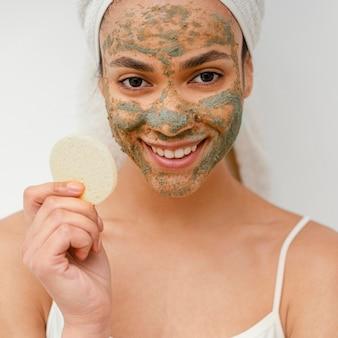 Счастливая женщина с домашней маской на лице