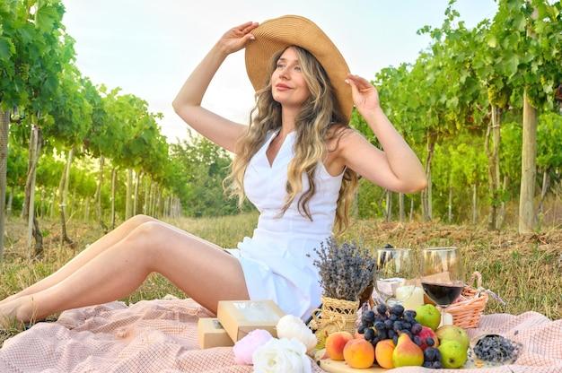 Счастливая женщина, пикник в винограднике. улыбка в большой шляпе и мечтательный вид