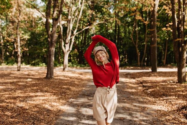 秋の公園で楽しい時間を過ごしている幸せな女性。落ち葉の中でポーズをとる金髪の笑顔。