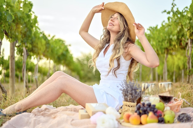 Happy woman having a picnic in the vine yard. big hat smilling and dreamy looks