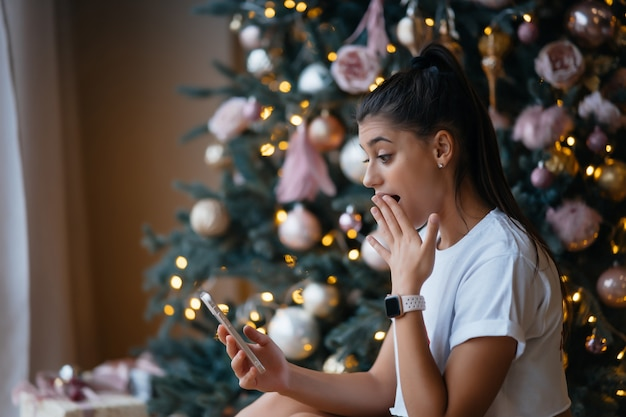 Donna felice che ha una videochiamata con la famiglia o gli amici. la giovane donna utilizza una tavoletta digitale vicino all'albero festivo decorato a casa.