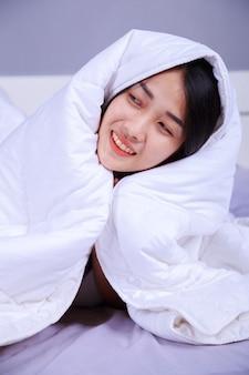 침실에서 침대에 담요 아래에 숨어있는 행복한 여자