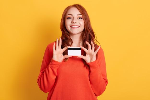 행복 한 여자 손에 신용 카드를 잡고, 쇼핑을 할 준비가 되 고, 주황색 스웨터를 입고, 노란색 배경, 그녀의 신용 카드를 보여주는 은행의 클라이언트 위에 절연 포즈.