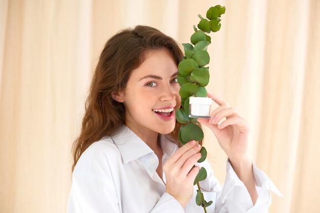 Счастливая женщина держит банку крема возле лица с эвкалиптом