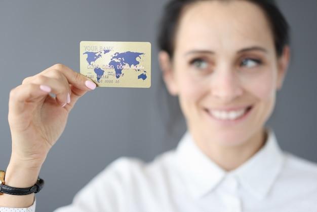 幸せな女性はプラスチックのクレジットカードを保持します