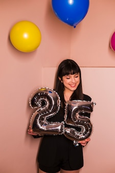 Happy woman holding 25 foil birthday balloon