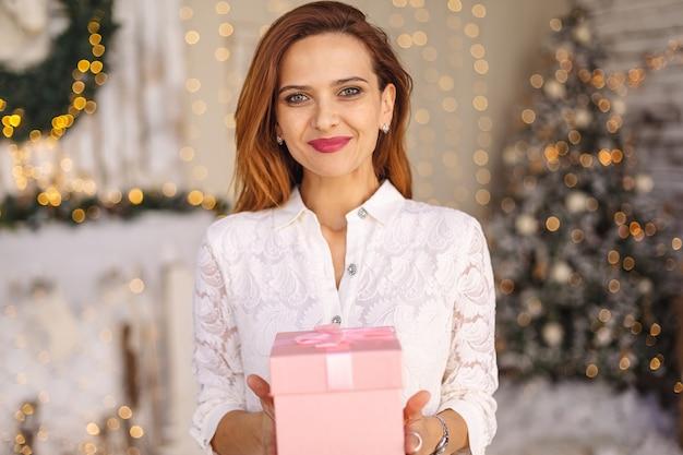 Счастливая женщина держит подарочную коробку
