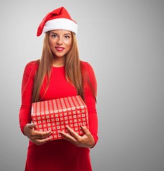 Счастливая женщина, держащая подарок обеими руками