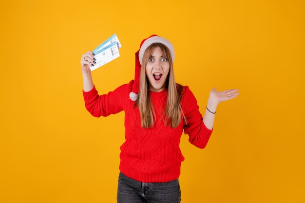 Happy woman holding airplane tickets wearing santa hat