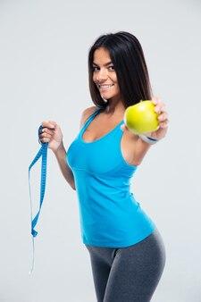 Счастливая женщина, держащая яблоко и измерительная лента