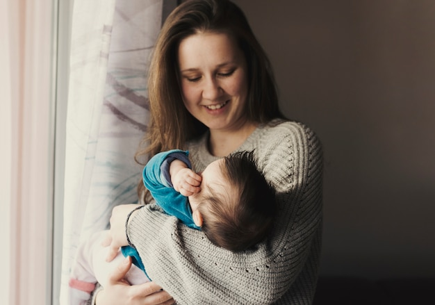 Happy woman holding baby in arms