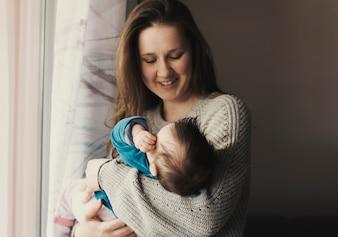 幸せな女持株赤ちゃんの腕の中で
