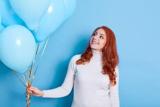 風船を持って、誕生日のサプライズに笑顔を見て幸せな女性