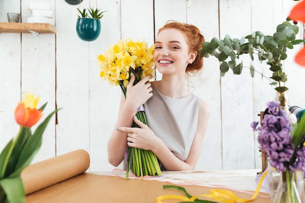 Happy woman holding beautiful bouquet of yellow flowers while working