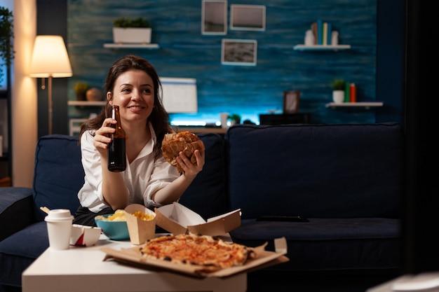 Donna felice che tiene la bottiglia di birra che mangia consegna di cibo da asporto gustoso
