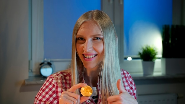 Happy woman holding bitcoin showing thumbs up. cheerful young blond woman in casual clothes sitting at dark window at night holding bitcoin and doing thumbs up gesture smiling and looking at camera.