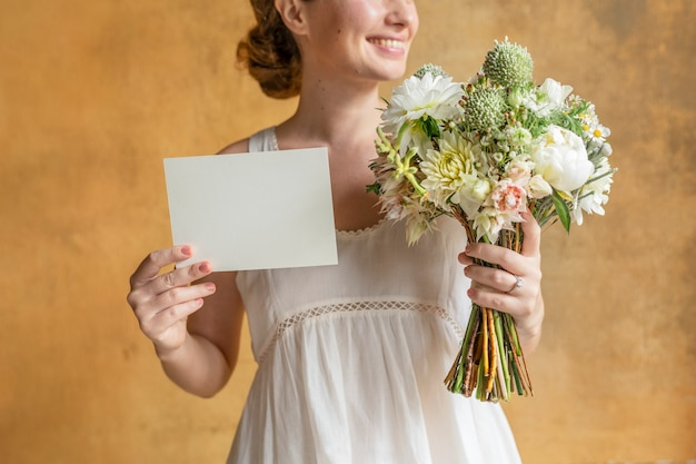 Happy woman holding a blank card with a bouquet of flowers