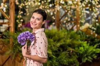 緑の家で青い花を持って幸せな女