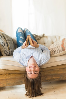 Happy woman holding book while lying on sofa