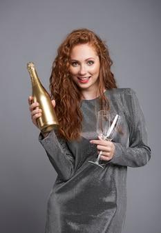 Donna felice che tiene una bottiglia di champagne e champagne flute