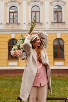 春に屋外の花の花束を保持している幸せな女性