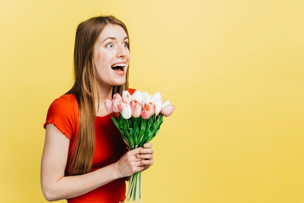 Happy woman holding a bouquet of tulips with copy space