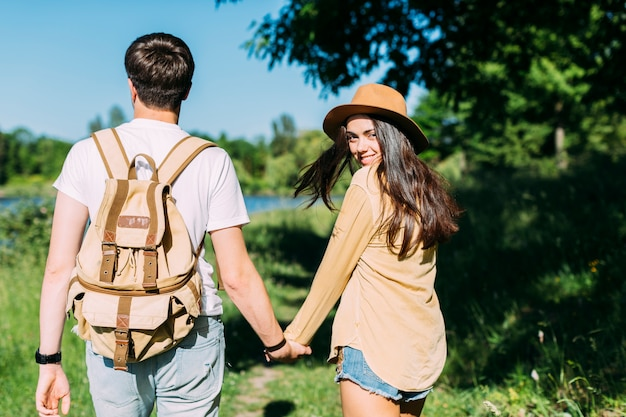 Happy woman holding boyfriend's hand looking at camera
