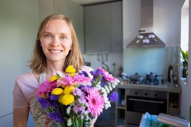 花の束を持って、家庭の台所でポーズをとって、カメラ目線と笑顔の幸せな女。女性の日や特別な日付のコンセプト