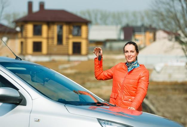 자동차와 집 열쇠를 들고 행복 한 여자